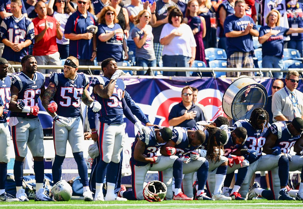 Some members of the New England Patriots stand during the National Anthem while others kneel before a game against the Houston Texans at Gillette Stadium on September 24, 2017 in Foxboro, Massachusetts. (Billie Weiss/Getty Images)