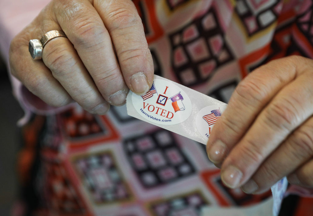 """A voter in Texas hands out """"I voted"""" stickers"""