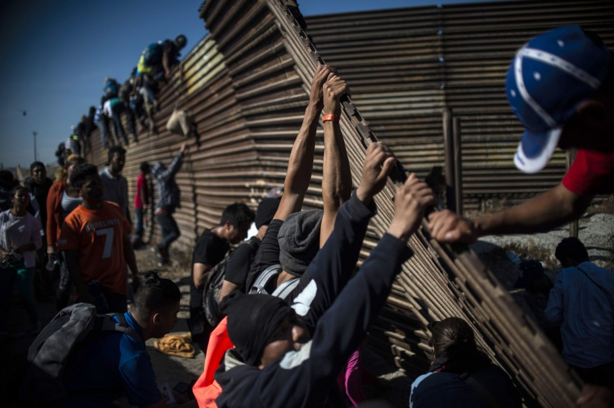 migrants trying to scale U.S. border