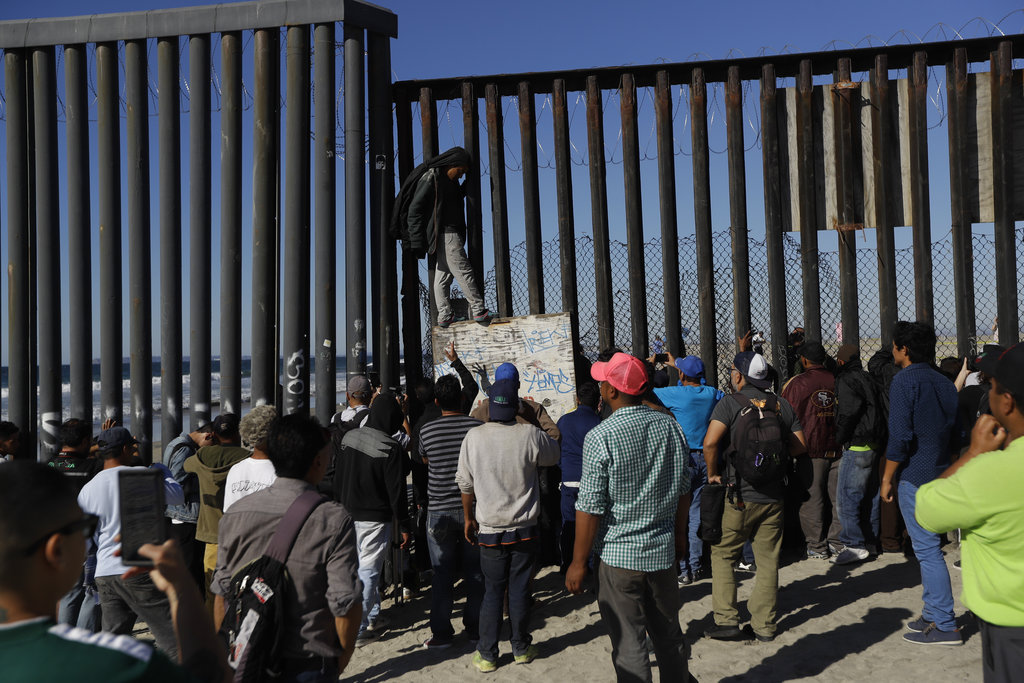 Migrants at Tijuana border fence