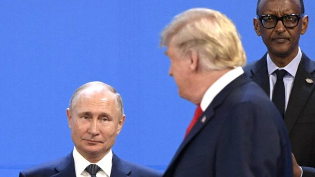 US President Donald Trump (R), looks at Russia's President Vladimir Putin
