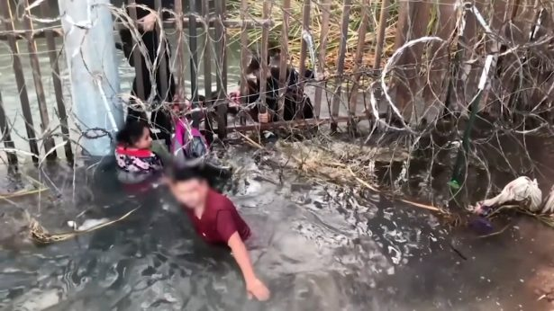 Migrants go under border