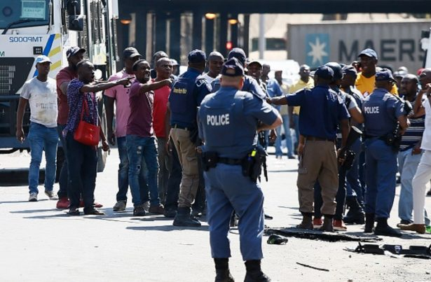 Minibus taxi drivers argue with South African Police Service members during a taxi drivers' riot near the Bloed Taxi Rank