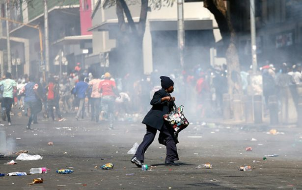 A woman runs for cover during the rioting of taxi drivers near the Bloed Taxi Rank