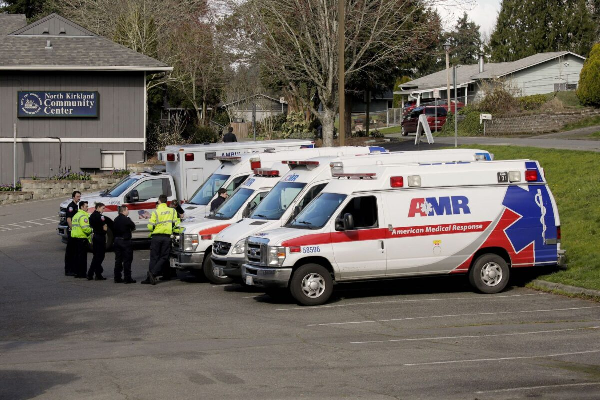 Ambulances are seen in a staging area