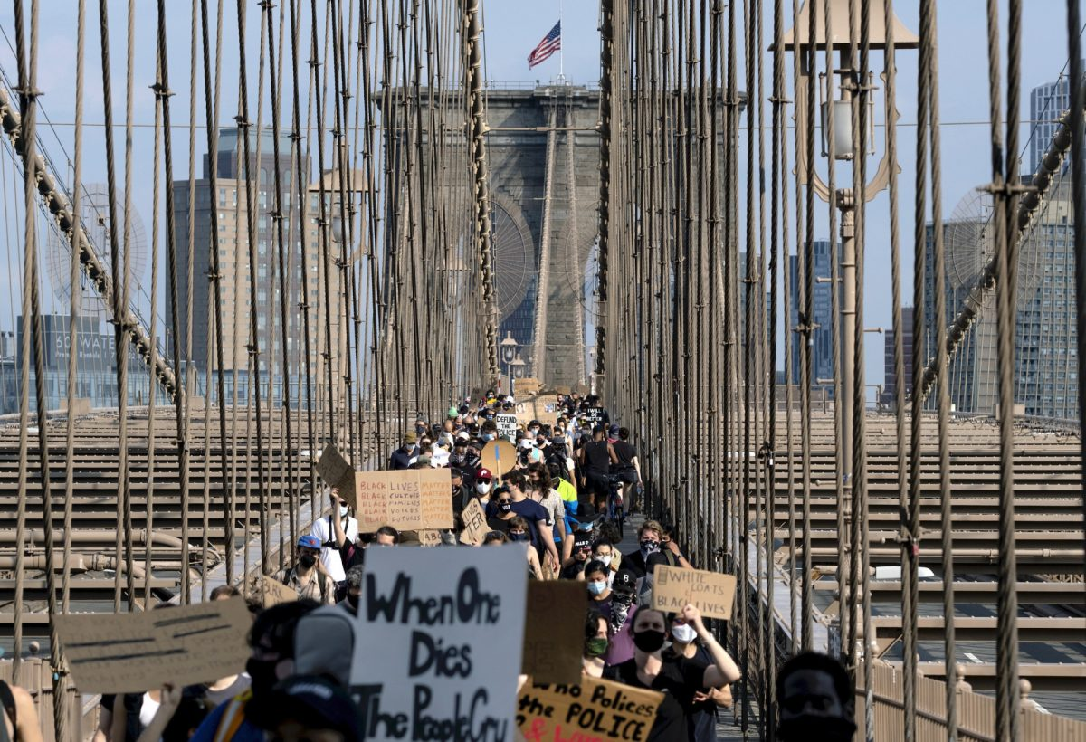 Protesters and activists walk across the Brooklyn Bridge
