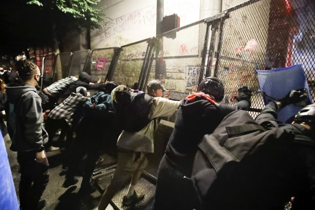 Rioters push fence
