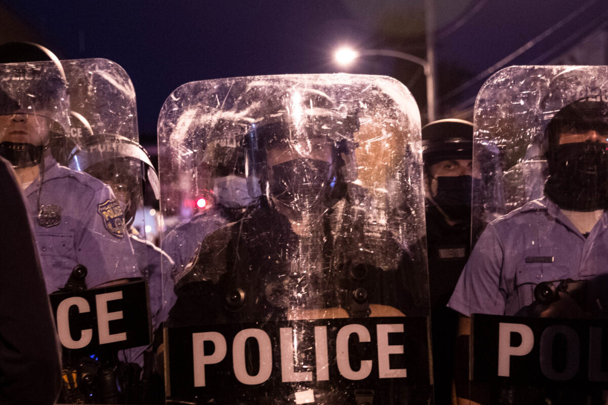 Police in riot gear face protesters