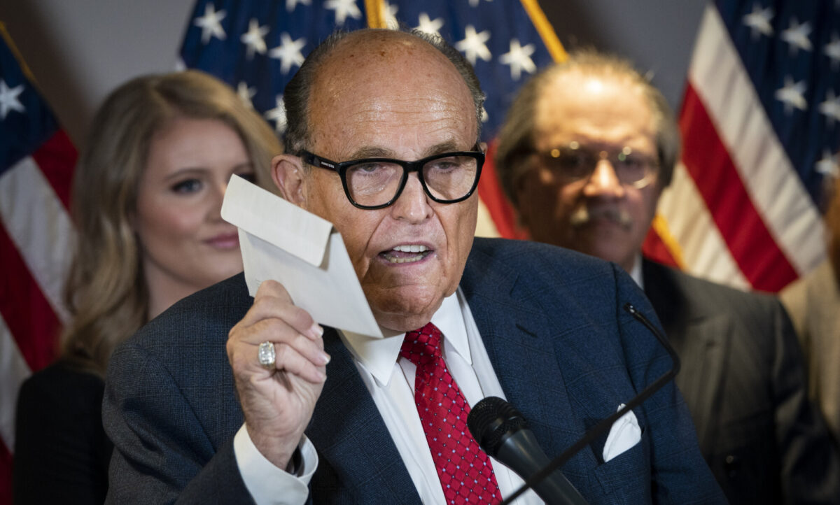 Rudy Giuliani holds up a mail-in ballot