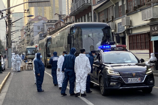 Police and workers stand next to buses