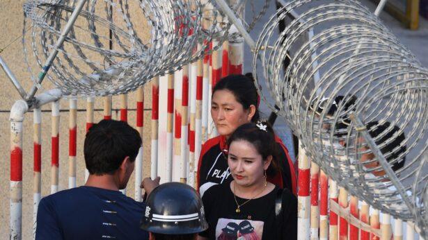 A Uighur woman (C) goes through an entrance
