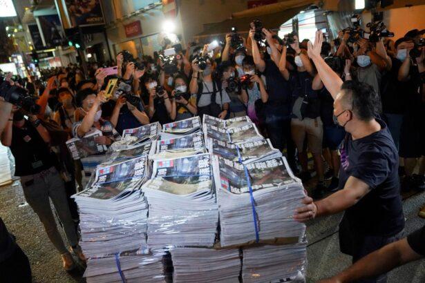 A man gestures as he brings copies