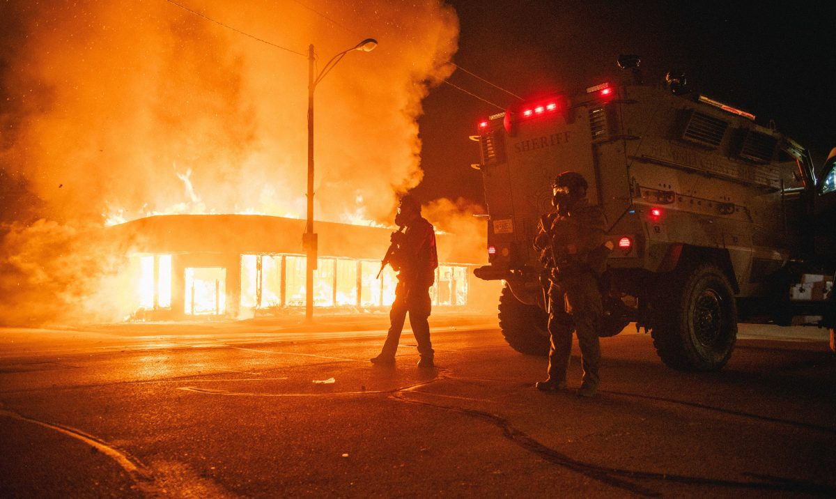 A police armored vehicle patrols an intersection while a building set afire