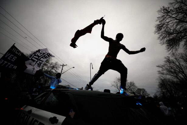 A demonstrator jumps off a police cruiser