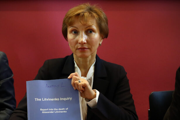 Marina Litvinenko holds a copy of a report at a press conference in her lawyer