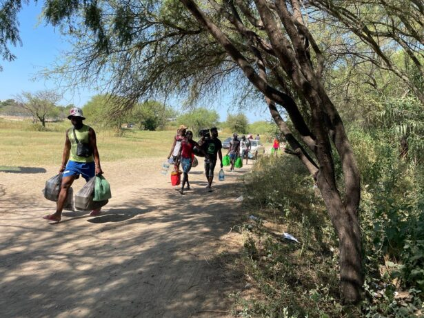People carry supplies from Acuna